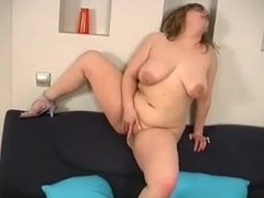 redhead girl on the couch pumps her pussy