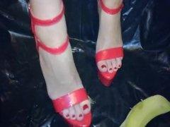 Hot red high heels crush a banana