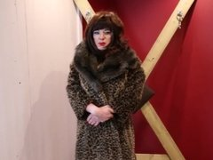 Domme Sindy in fur coat in the dungeon playroom
