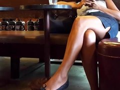 fr's crossed sexy long tanned legs in mini skirt