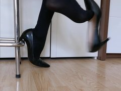 Shoe dangling and dropping black high heeled pumps in nylons