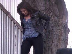 Brunette in black leggings pisses outdoors