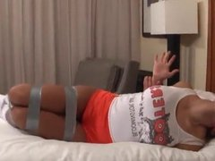 Sexy Hooters Girl in Tape Bondage and gagged on Bed
